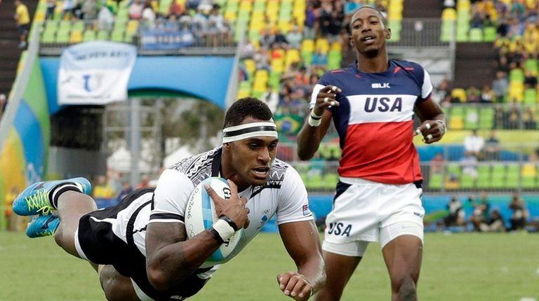 Fiji's Semi Kunatani, left, scores a try as