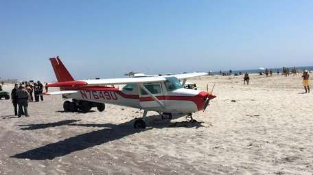 A small plane sits in the sand at