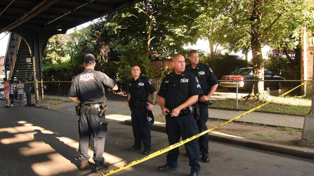NYPD officers investigate the shooting of two men