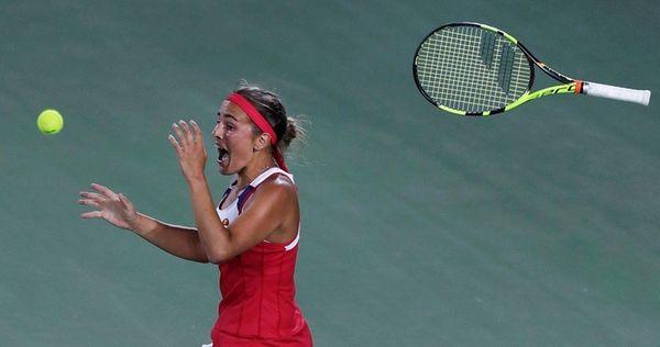 Monica Puig, of Puerto Rico, tosses her racquet