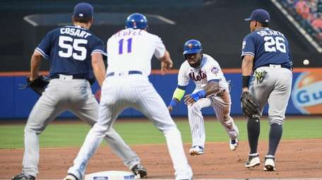 Jose Reyes charges into third base in the