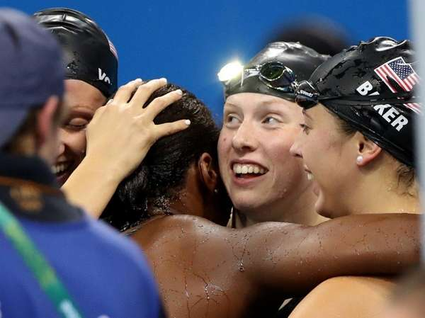 United States' swimmers celebrate their gold in the