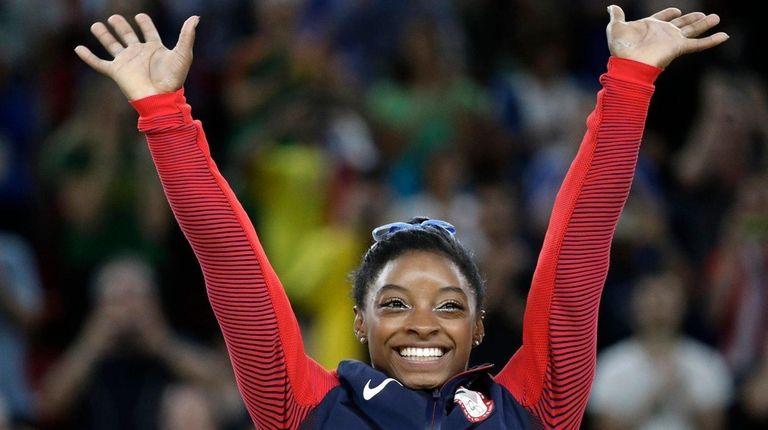United States' Simone Biles, gold medal winner, waves