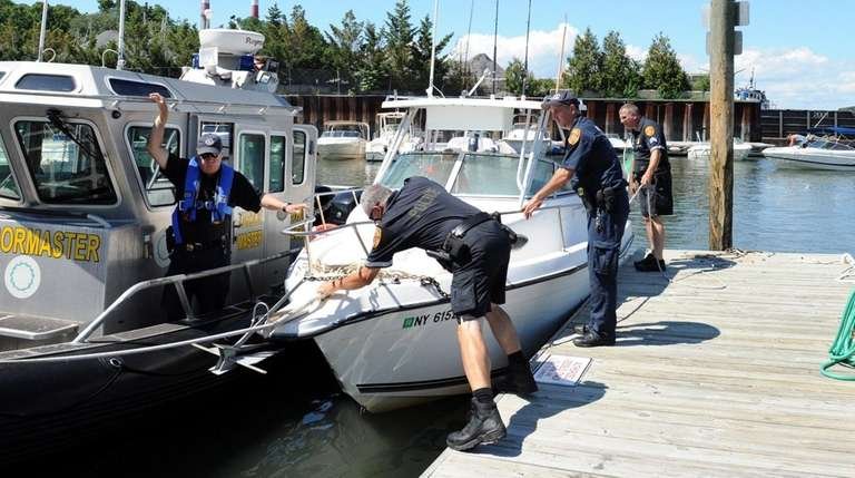 Suffolk police officers secure a boat to a