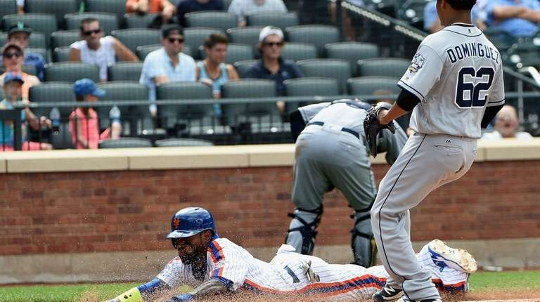 The Mets' Jose Reyes scores on a wild