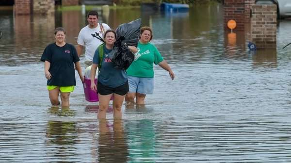 People wade in water near flood-damaged homes in