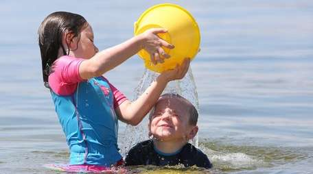 Quinn McNally, of Northport, 6, left, dumps a