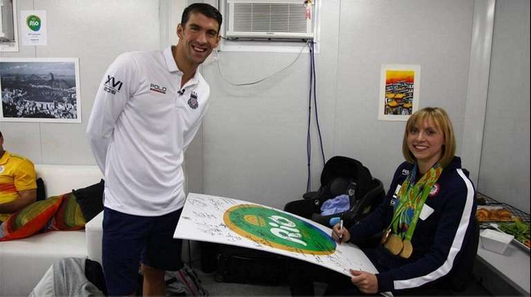 Top: Michael Phelps signs an autograph for Katie