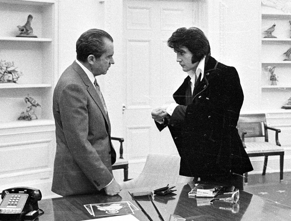 Elvis Presley shows President Richard Nixon his cuff