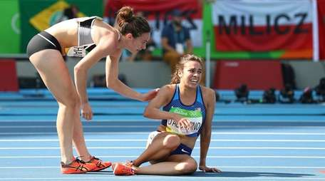 Abbey D'Agostino of the United States, right, assisted