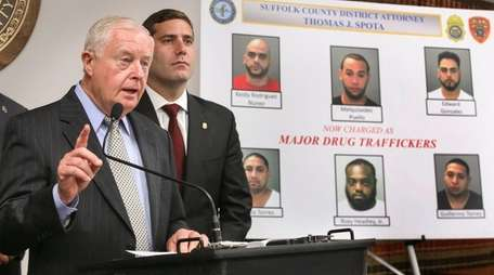 Suffolk County District Attorney Thomas Spota, left, speaks