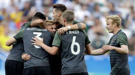 Germany's players celebrate after Germany's Lukas Klostermann scored