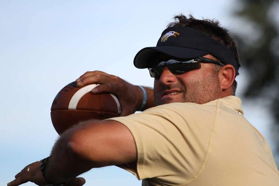 Coach Michael Lewis throws a pass during practice