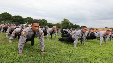 Nassau County police recruits participate in a 22-push-up