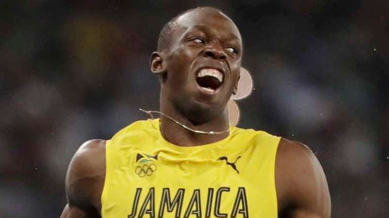 Usain Bolt from Jamaica, left, celebrates after crossing