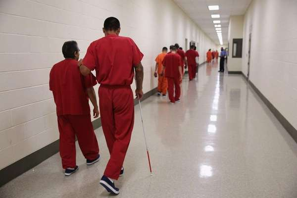 A blind detainee walks with a fellow immigrant