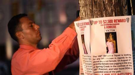 A Crime Stoppers officer hangs rewards posters outside