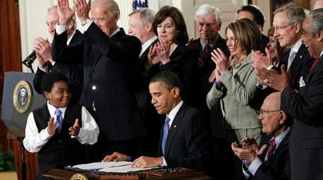President Barack Obama is applauded after signing the