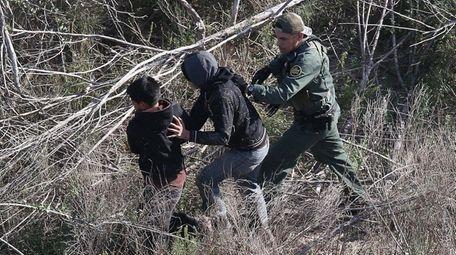 A U.S. Border Patrol agent detains juvenile immigrants