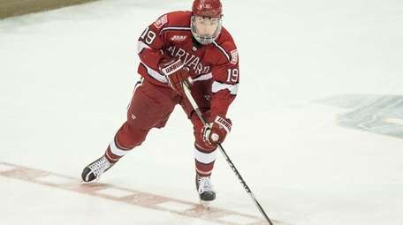Harvard Crimson forward Jimmy Vesey brings the puck