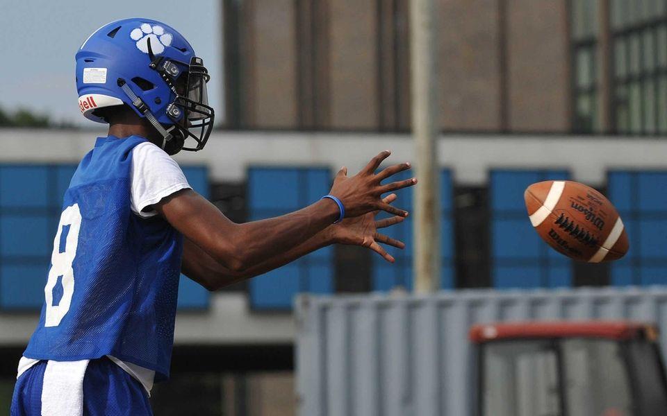 Saybien Barron #8, Hempstead quarterback, takes a snap