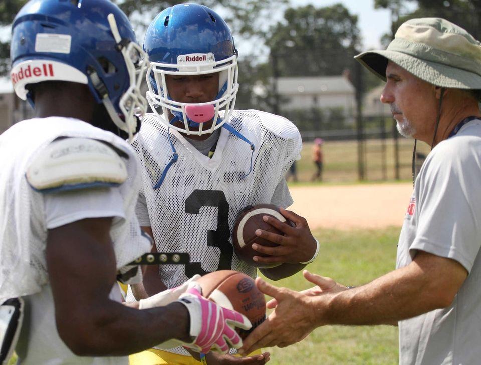 Players give footballs to head coach Joe Vito