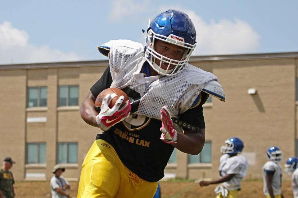 Chavcer McMillan runs with the football during practice