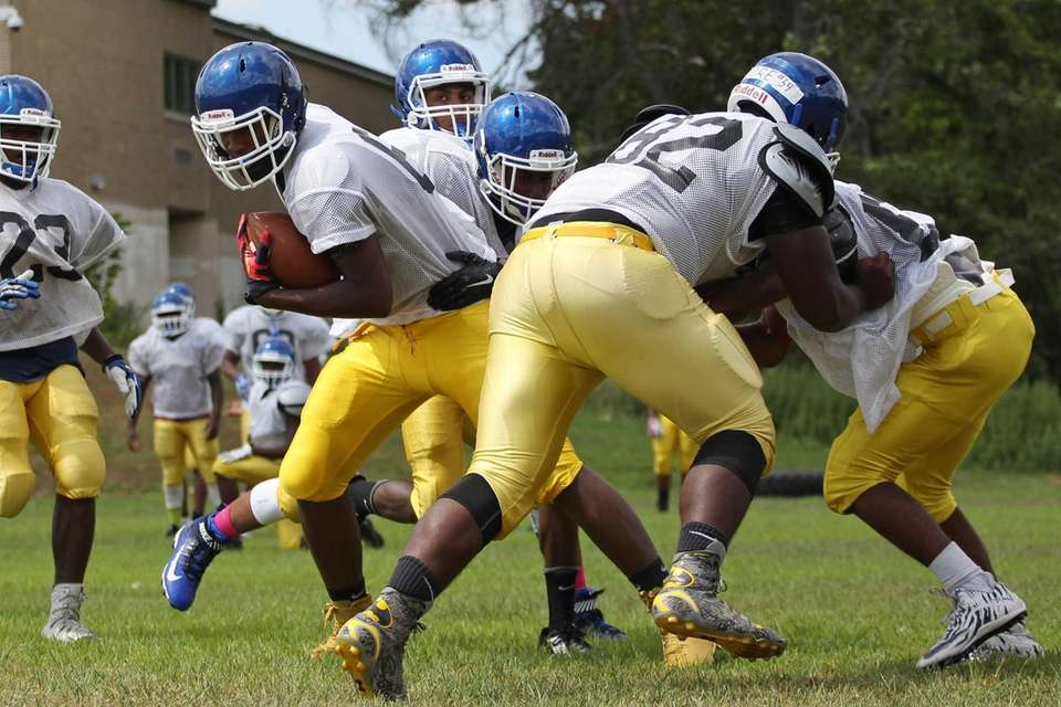 Players fight for the football during practice at
