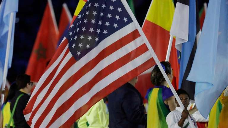 Simone Biles carries the flag of the United