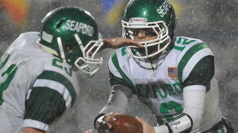 Seaford quarterback Andrew Cain, right, hands off to