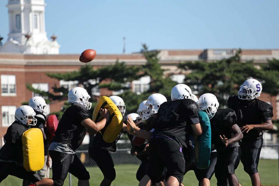 Players do a blocking drill during practice at