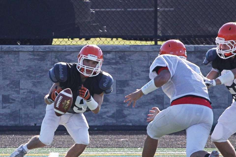 Antonio Roselli runs with the football during practice