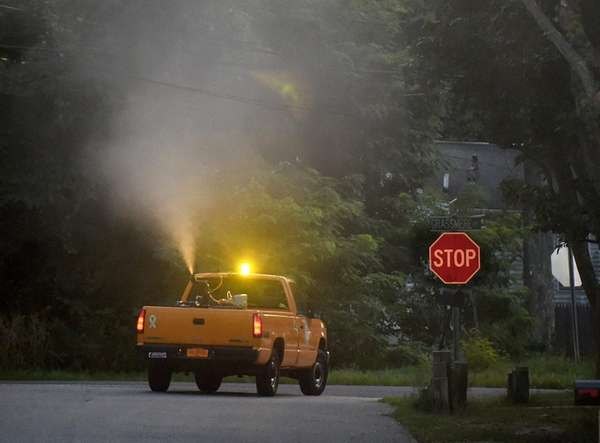 A Suffolk County public works vehicle ground sprays