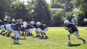 Members of the Massapequa football team run drills