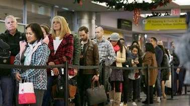Passengers wait to pass through airline security at