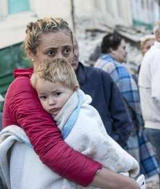 A mother embraces her son in Amatrice in