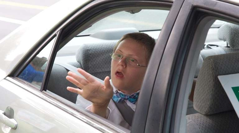 Aiden Killoran sits in a car in front