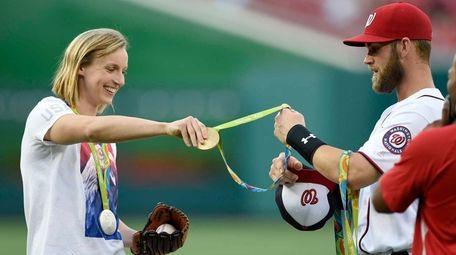 Olympic gold medal swimmer Katie Ledecky, left, hands