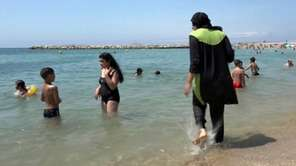 Nissrine Samali, 20, goes in the ocean wearing