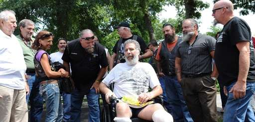 Jack Monti, 49, center, is surrounded by members