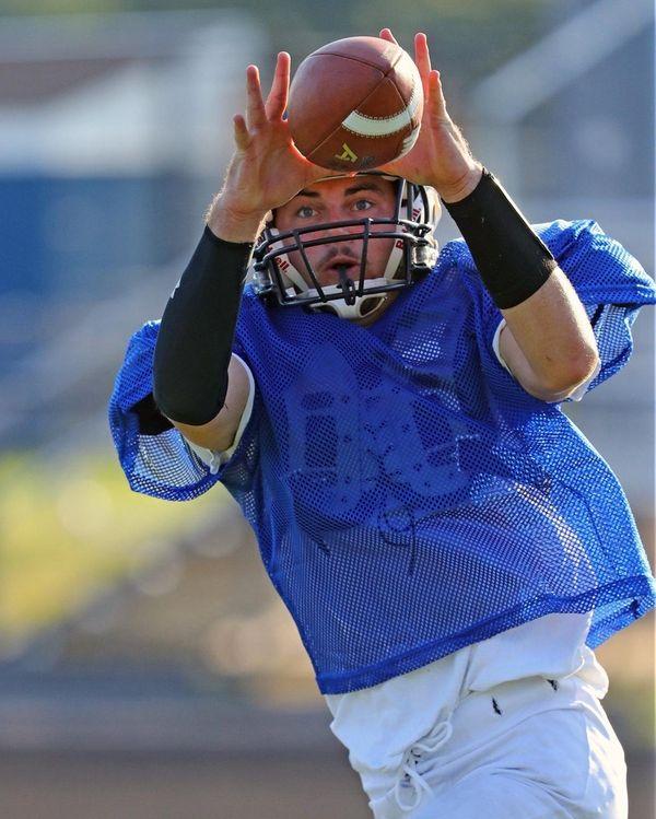 Centereach's Shawn McFarland catches a pass during football