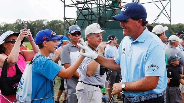 Phil Mickelson greets fans during the second round