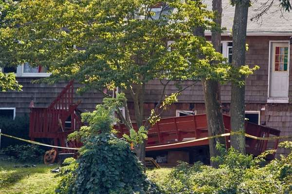 Police tape surrounds a deck that fell to
