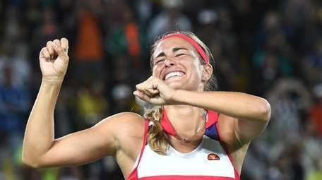 Monica Puig of Puerto Rico celebrates defeating Angelique