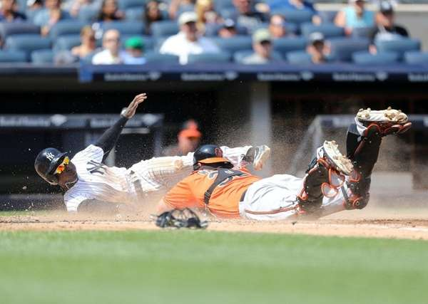 Yankees' Didi Gregorius dives for home plate past