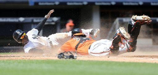 Yankees' Didi Gregorius dives for home plate past