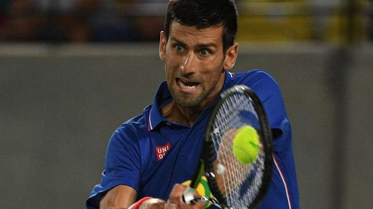 Novak Djokovic hits a backhand return to Juan