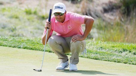 Adam Scott of Australia looks over a putt