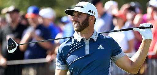 Dustin Johnson watches his tee shot from the