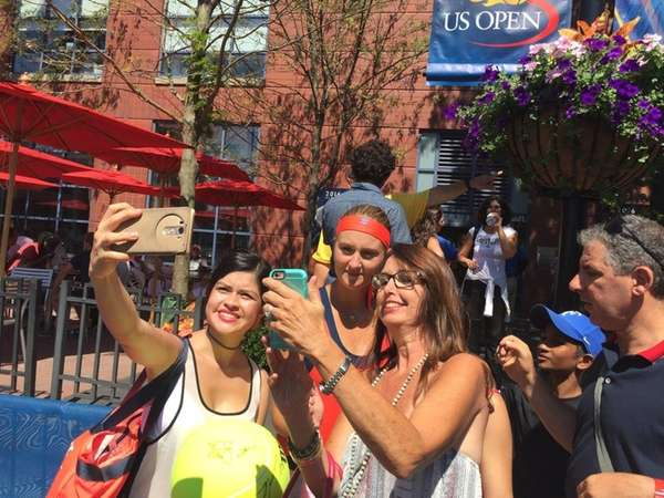 France's Kristina Mladenovic takes photos with fans a